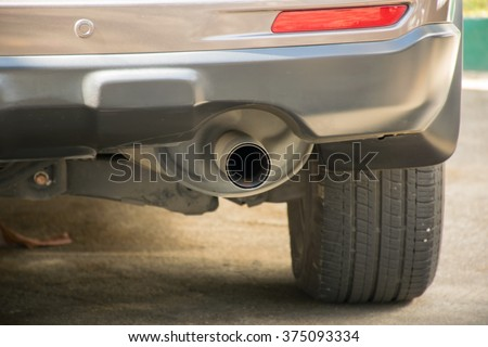 Exhaust pipe of a whited car - stock photo