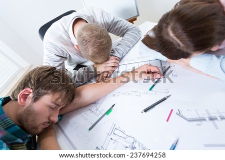 Exhausted architects fell asleep while working - stock photo