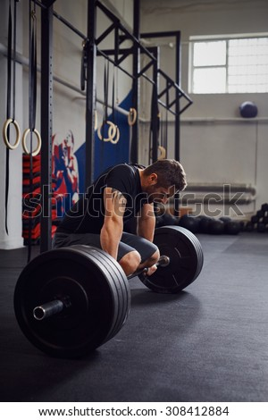 Exhausted athlete resting after heavy barbells training - stock photo