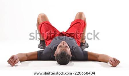 Exhausted athletic man lying down on white background. - stock photo