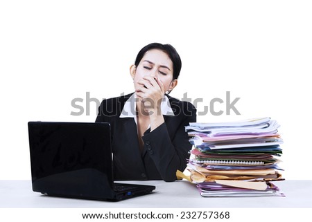 Exhausted attractive businesswoman working with her notebook sitting at her desk - stock photo
