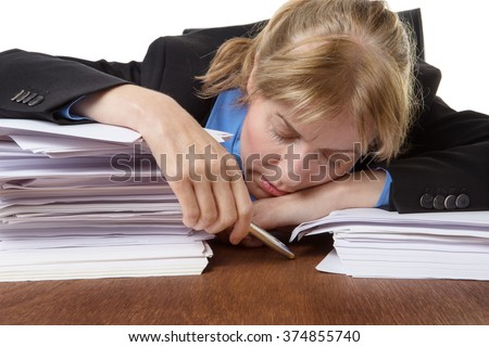 Exhausted business woman has fallen asleep on the desk behind some piles of paperwork - stock photo
