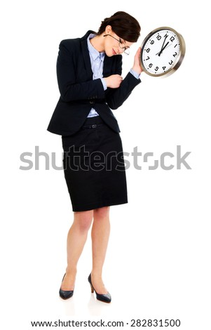 Exhausted business woman holding clock in hands.
