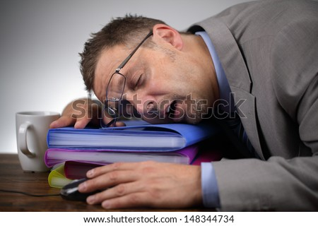 Exhausted businessman falling asleep at his office desk - stock photo