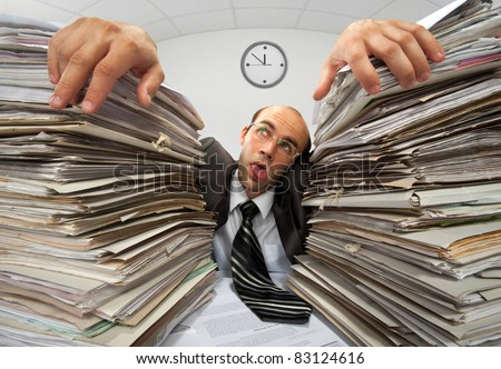 Exhausted businessman has had too much of his paperwork - stock photo