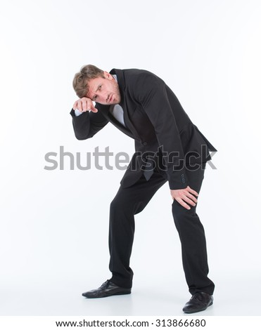 Exhausted businessman looking at the camera. Handsome man in black business suit resting after hard working day. - stock photo