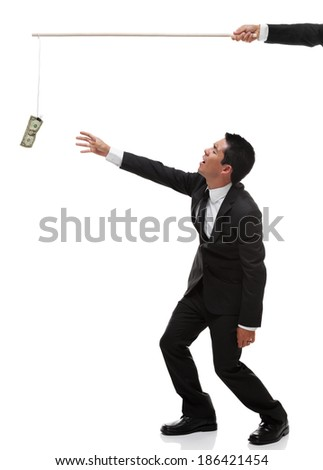 Exhausted businessman reaching for money on the end of a stick full body - stock photo