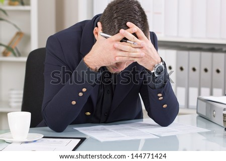 exhausted businessman sitting in an office - stock photo