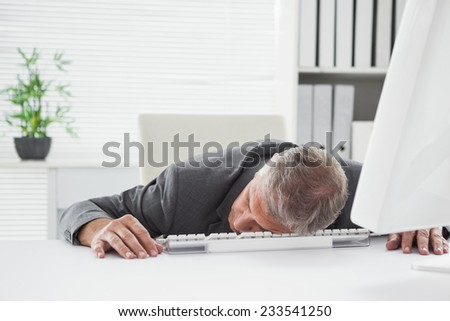 Exhausted businessman sleeping at his desk in his office - stock photo