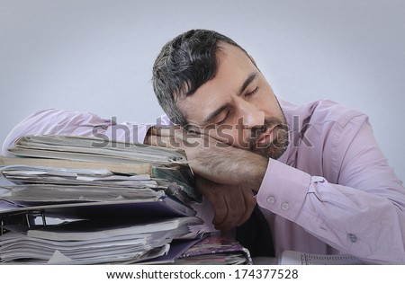 Exhausted businessman with a beard asleep at his desk with his head resting on a large stack of office files and paperwork - stock photo