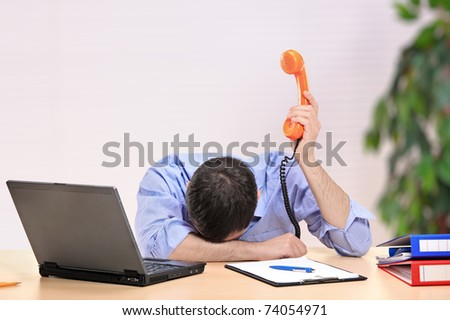Exhausted businessman with face down holding a telephone in an office - stock photo