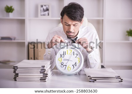 Exhausted businessman with glasses on forehead is holding the clock. - stock photo
