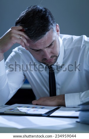 Exhausted businessman working at office at night - stock photo