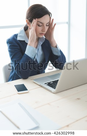 Exhausted businesswoman in her office with head in hands, she is having a bad headache, overwork and stress concept - stock photo