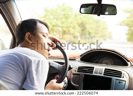 Exhausted driver resting on steering wheel in the car - stock photo