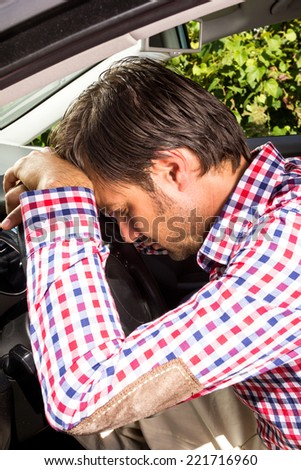 Exhausted driver resting on steering wheel of his car - stock photo
