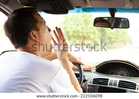 Exhausted driver yawning and driving car on the road.Transportation concept  - stock photo