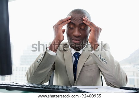 Exhausted entrepreneur working with a computer in his office - stock photo