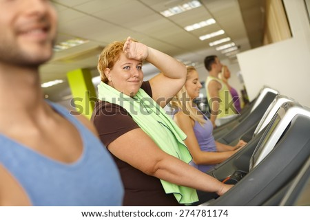 Exhausted fat woman training on running machine in gym. - stock photo