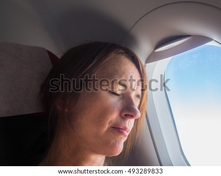 Exhausted female airplane passenger is sleeping at her seat in the airplane