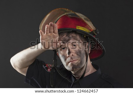 Exhausted Fireman wiping his dirty forehead using his hand