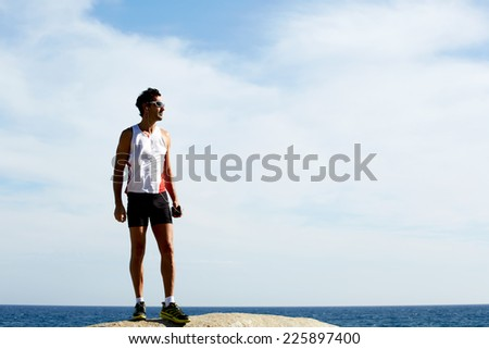 Exhausted fit runner after workout resting on seaside, sportsman listening to music with headphones, athlete standing on sea rocks at sunny summer day while resting after intensive training outdoors - stock photo