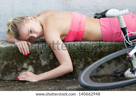 Exhausted girl laying on the ground after bicycle race