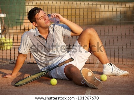 Exhausted male tennis player sitting on ground after tennis game, refreshing, cooling himself. - stock photo