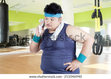 Exhausted man after workout and wiping his sweat at gym - stock photo