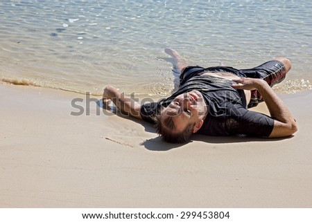 exhausted man crawled out of the sea and lying on the beach - stock photo