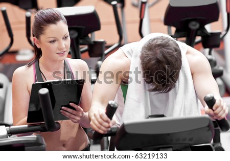 Exhausted man doing exercises while his coach is looking at his results in a sport centre - stock photo