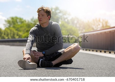 Exhausted man resting after jogging in full sun