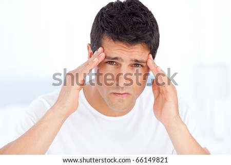 Exhausted man suffering from a headache in his bedroom - stock photo