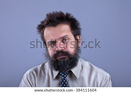 Exhausted man with bushy hair and beard on gray background - copy space
