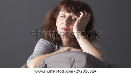 exhausted mature woman resting her face and hands laying down on cushions for comfort while being sick or depressed