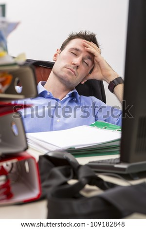 Exhausted office worker falls asleep in front of his computer, surrounded by a pile of file folders - stock photo