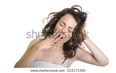 Exhausted or bored woman in yawn.Young woman yawning with her hand to her mouth and closed eyes, isolated on white.