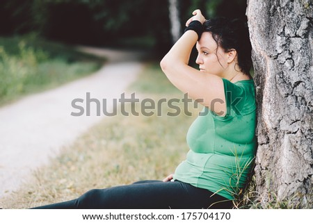 Exhausted overweight woman sitting down after training - stock photo
