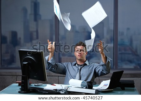 Exhausted professinal throwing documents into air sitting at office desk in overtime. - stock photo