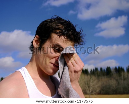 Exhausted runner taking a break and wiping his brow