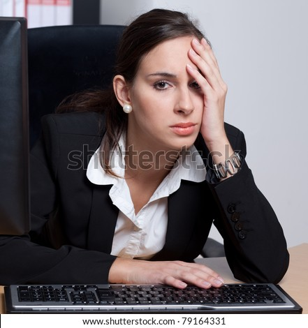 Exhausted, stressed businesswoman in her office - stock photo