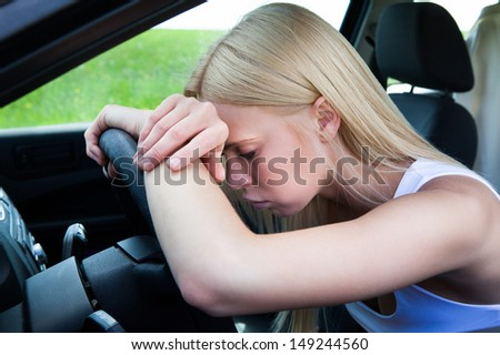 Exhausted Woman Leaning Head On Steering Wheel - stock photo