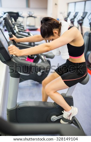 Exhausted woman on the exercise bike at the gym