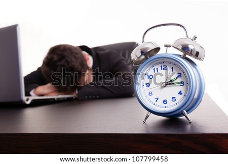 Exhausted young business man sleeping next to his laptop at the desk, isolated on white - stock photo