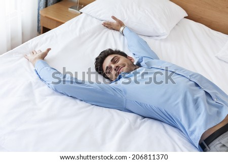 Exhausted young businessman lying in bed - stock photo
