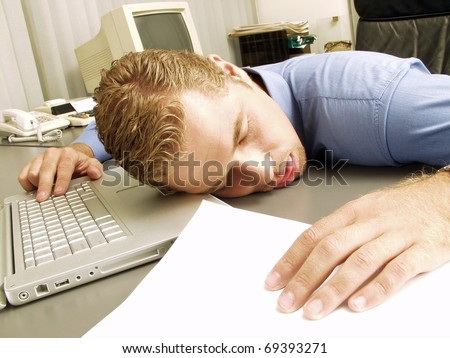 exhausted young businessman sleeping at his desk. - stock photo