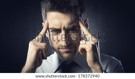 Exhausted young businessman with headache touching his head.