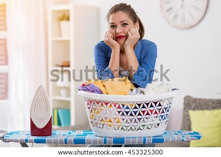 Exhausted young housewife taking a break from ironing - stock photo