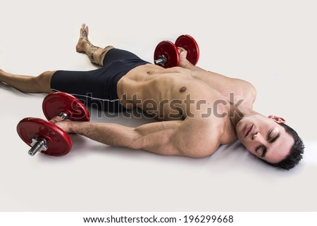 Exhausted young male bodybuilder resting on floor with dumbbells in hands - stock photo
