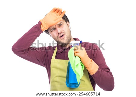 Exhausted young man with apron and gloves holding  cleaning sprayer and cloth over white - stock photo